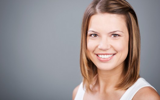 Portrait of happy brunette woman on a grey wall background